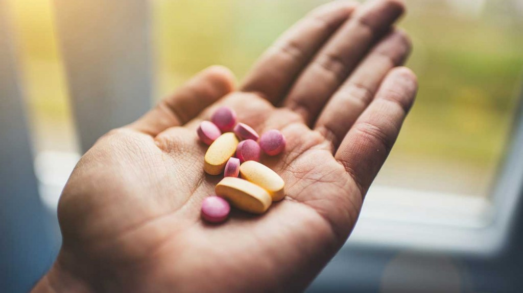 hand-holding-yellow-and-pink-pills